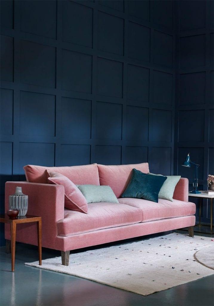 Salón pared azul marino sofá rosa