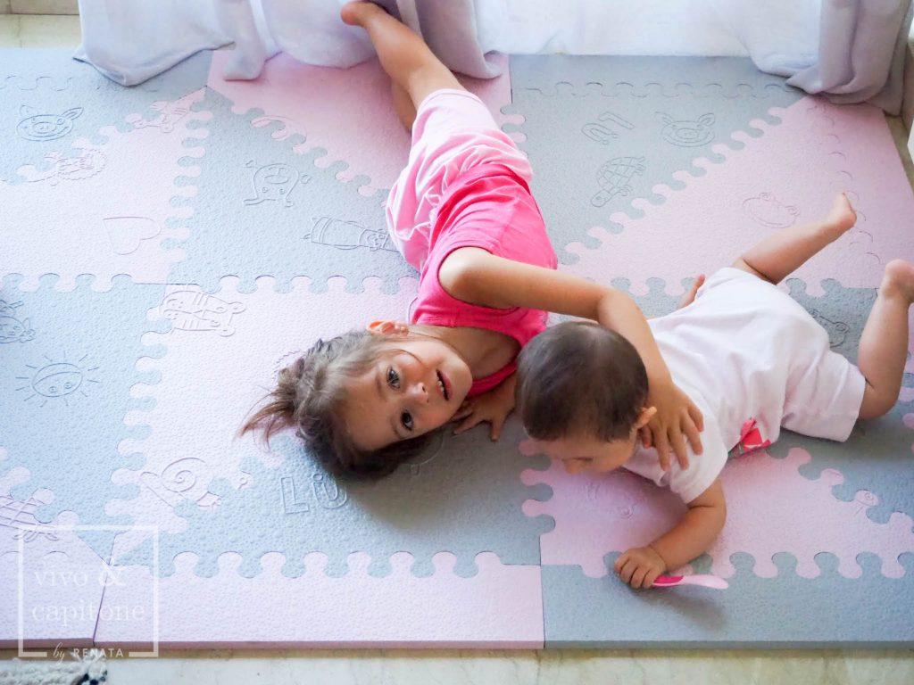claudia y sofia jugando en la alfombra para bebes